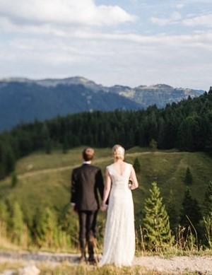Brautpaar Hand in Hand mit Blick über das Urpsrungtal vor Bergpanorama