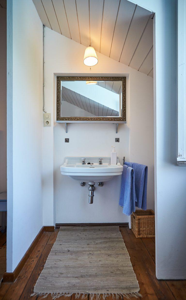 Waschbecken und Spiegel im Gästezimmer des Almbad Sillberghaus