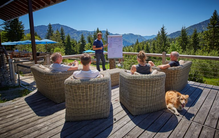 Coach erklärt am Flipchart, umgeben von Tagungsgruppe am Naturpool