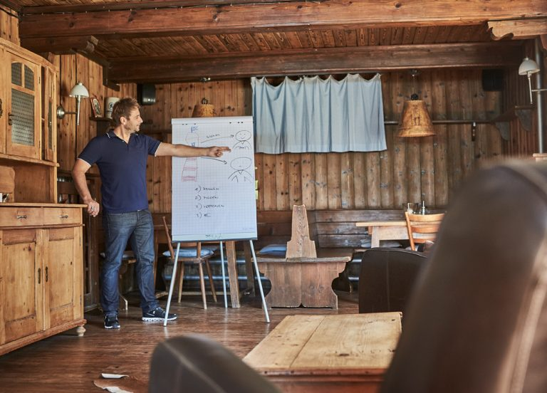 Coach am Flipchart im Kaminzimmer des Almbad Sillberghaus