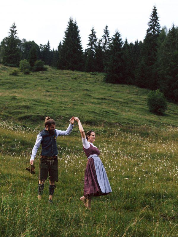 Tanzendes Brautpaar in bayerischer Tracht auf der Almwiese des Almbad Sillberghaus