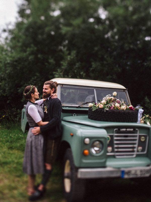 Brautpaar in Tracht mit türkisem Oldtimer LandRover