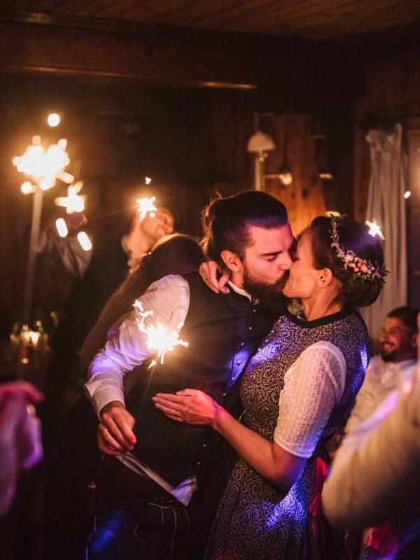 küssendes Brautpaar umgeben von Wunderkerzen im Kaminzimmer des Almbad Sillberghaus