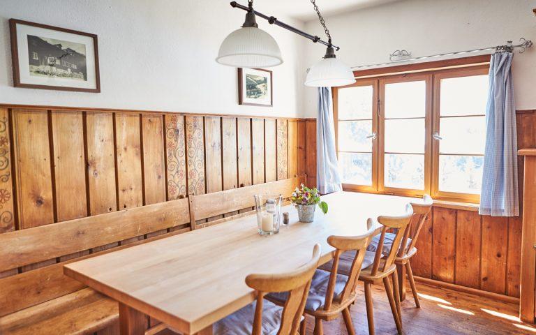 Helle Gaststube mit Holzwand und Holzfenster mit Blick ins Alpenpanorama des Ursprungtal