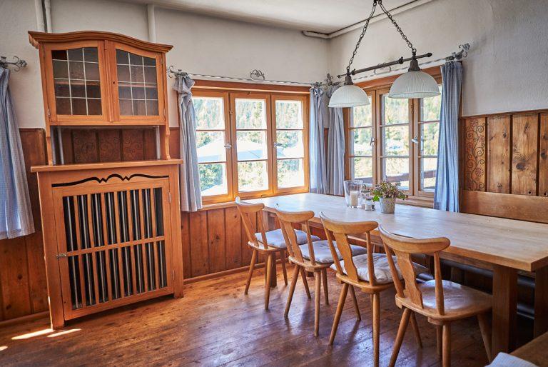 Helle Gaststube mit Holzstühlen und Holzfenster mit Blick zum Ursprungtal