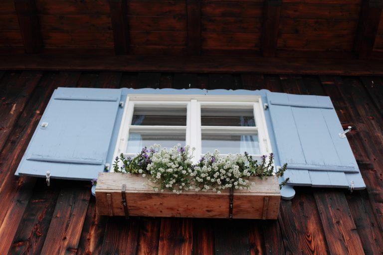 Hingucker: Das Almbad Sillberghaus mit blauen Fensterläden und Blumenkasten