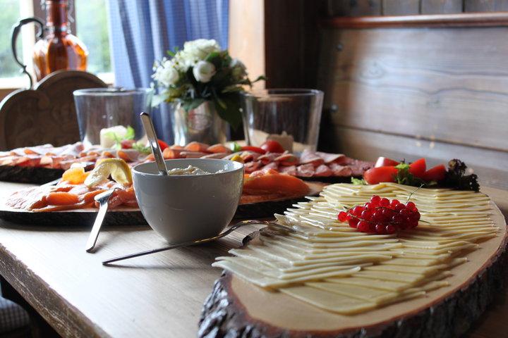 mit Käse, Fisch und Obst gedeckter Frühstücks-Tisch im Almbad Sillberghaus