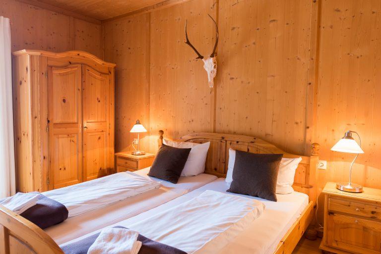 Doppelbett in der Almsuite mit Abendbeleuchtung