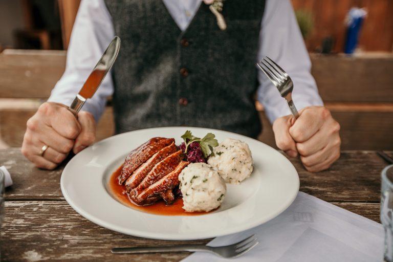 Ein Herr sitzt bereit zum Essen am Tisch, Messer und Gabel in der Hand - vor ihm ein BIO-Krustenschweinebraten mit Semmelknödel