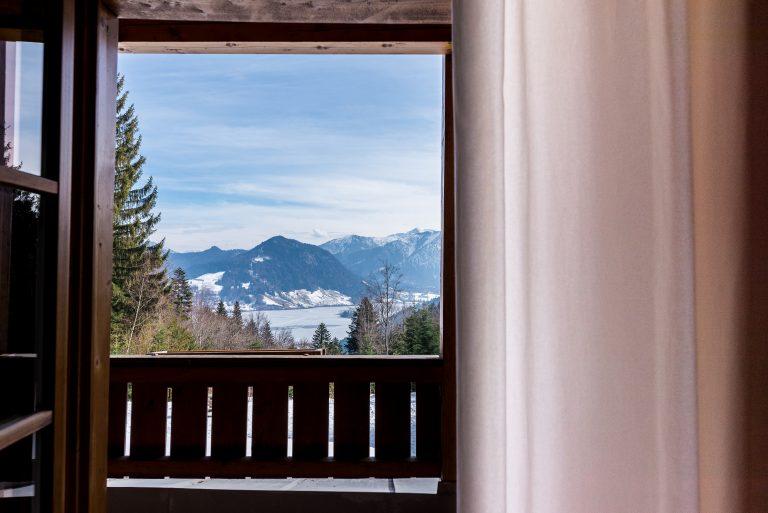 Blick aus dem Fenster auf den Schliersee vor Bergpanorama