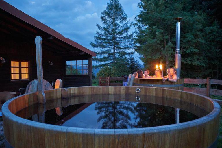 Zwei mit Wasser befüllte Hot Tubs vorm Almbad Huberspitz