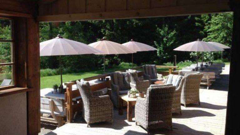Die Lärchenholzterrasse im Sommer mit braunen Sonnenschirmen und gemütlichen Gartengarnituren