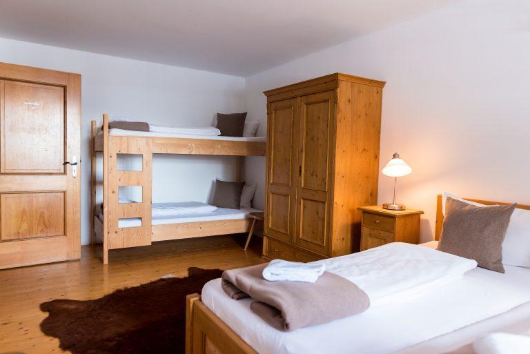 Blick in eine Almsuite im Almbad Huberspitz, mit Doppelbett und Stockbett