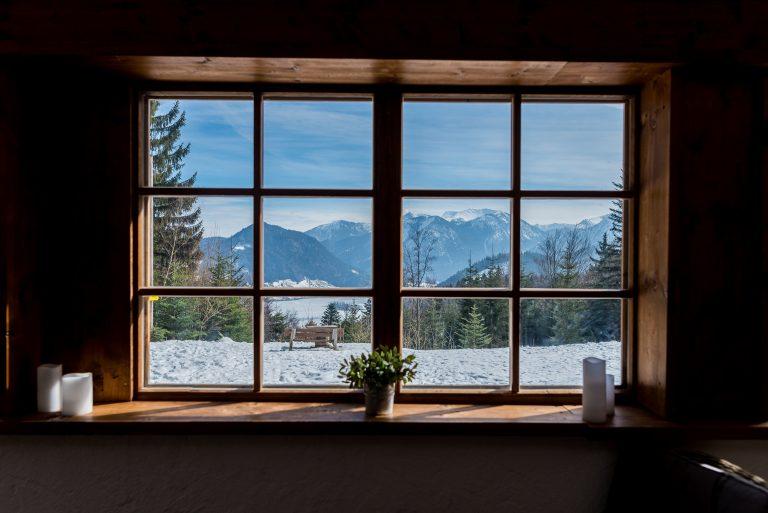 Blick aus dem Fenster ins verschneite Bergpanorama hinter dem Schliersee