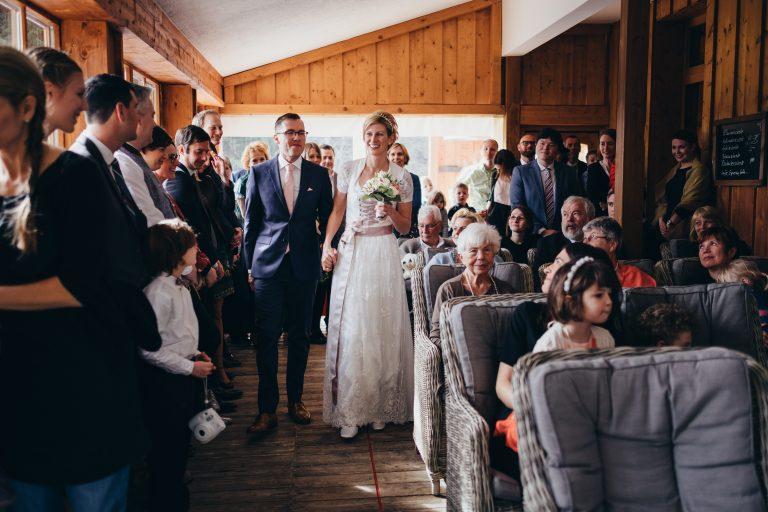 Brautpaar auf dem Weg durch den Trausaal durch ihre große Hochzeitsgesellschaft zur standesamtlichen Trauung