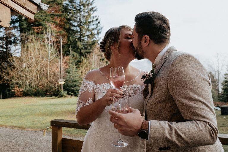 Brautpaar küsst sich vorm Almbad Huberspitz mit Gläschen Spritz vor Ausblick zum Schliersee