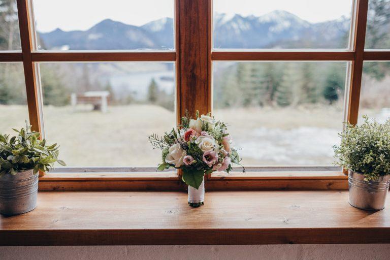 Blick aus dem Fenster auf den Schliersee vom Wintergarten (Trausaal) des Almbad Huberspitz, in der Mitte ein kleiner Blumenstrauß zur Fensterdekoration