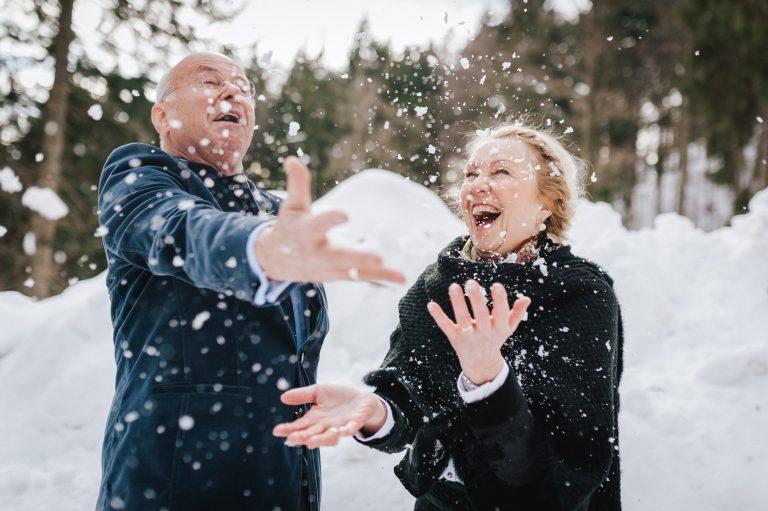 Brautpaar spielt lachend im Schnee am Almbad Huberspitz