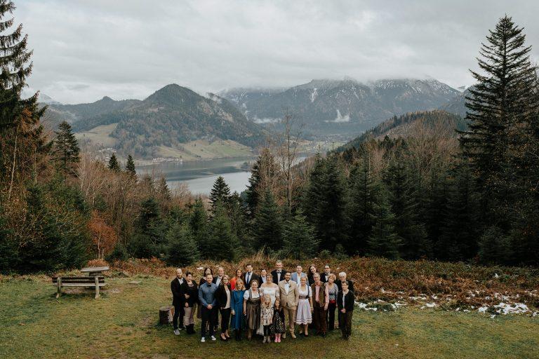 Gruppenbild einer Hochzeitsgesellschaft im Almbad Huberspitz in 1.050m Höhe mit Blick auf die Berge und das dahinter liegende Alpenpanorama