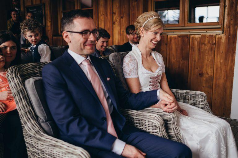 Das Brautpaar sitzt händchenhaltend vorm Trautisch, zur standesamtlichen Trauung im Almbad Huberspitz