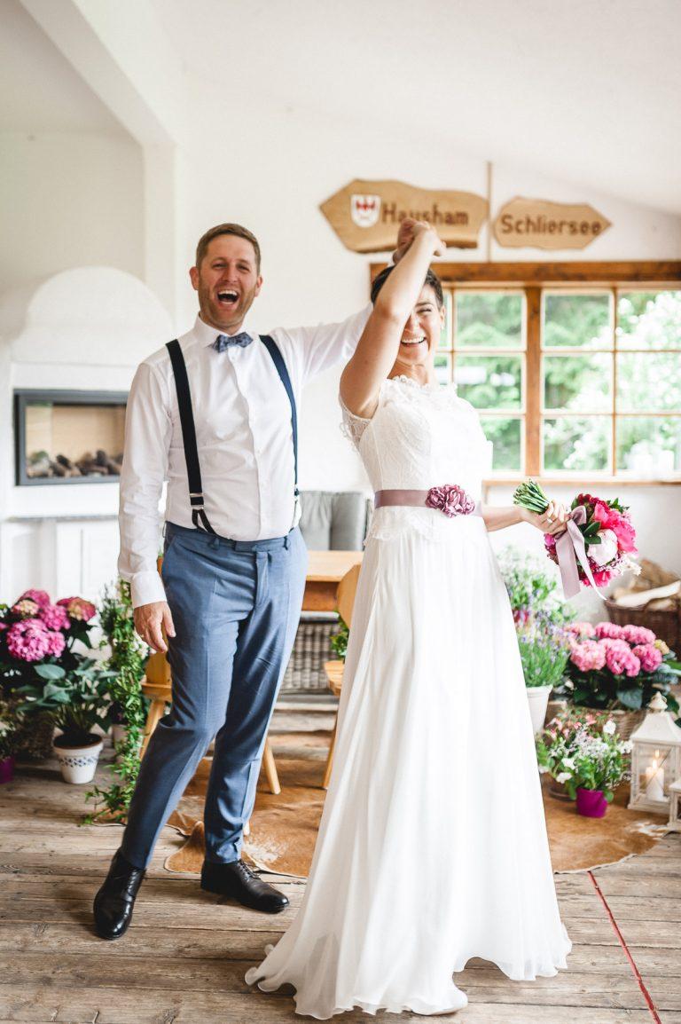 Das Brautpaar lacht beim Tanz im Trausaal des Berg-Standesamt Almbad Huberspitz in 1.050m Höhe