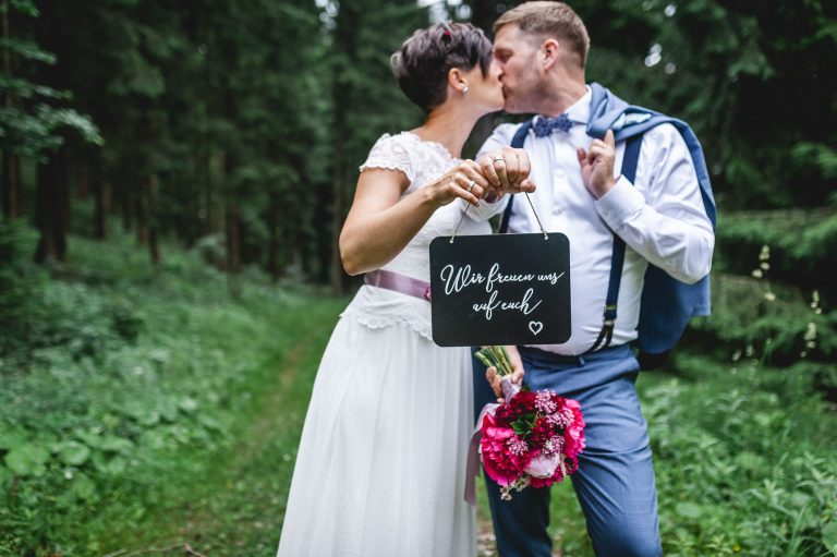 Brautpaar küsst sich im Bergwald des Almbad Huberspitz, mit Schild, das Wir freuen uns auf euch! schreibt