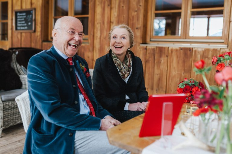 Lachendes Brautpaar am mit roten Blumen geschmückten Trautisch des Berg-Standesamts Almbad Huberspitz
