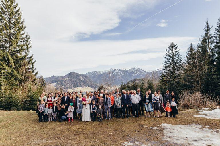 Große Hochzeitsgesellschaft im Almbad Huberspitz vor Bergpanorama und Blick zum Schliersee
