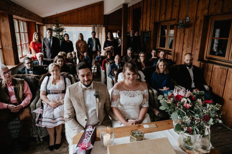 Ein glückliches Brautpaar feiert ihre Winter Hochzeit in den Bergen am Almbad Huberspitz mit Freunden und Familie