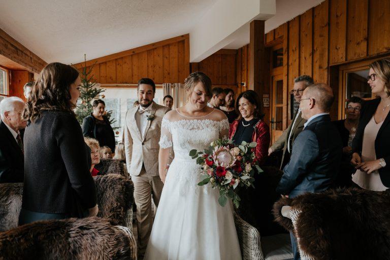 Braut und Bräutigam strahlen freudig bei ihrer standesamtlichen Trauung im Almbad Huberspitz dem Berg Standesamt in Bayern in der Nähe von München