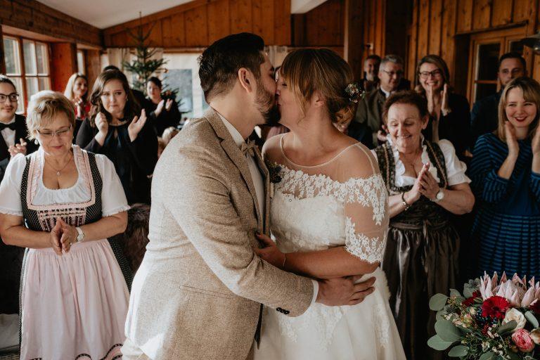Brautpaar küsst sich nach der standesamtlichen Trauzeremonie im Alm-Trausaal auf 1.050m im Almbad Huberspitz