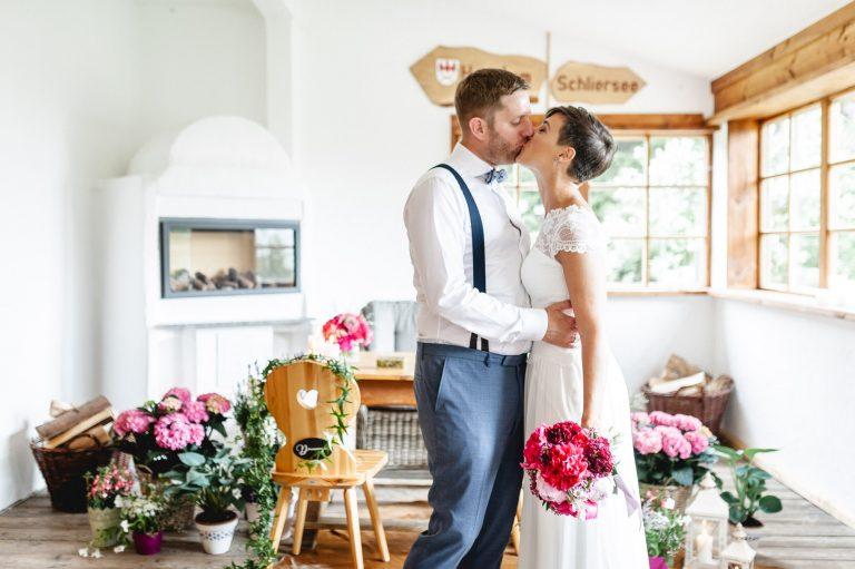 Das Brautpaar küsst sich vor dem floral dekorierten Trautisch im Almbad Huberspitz in 1.050m Höhe