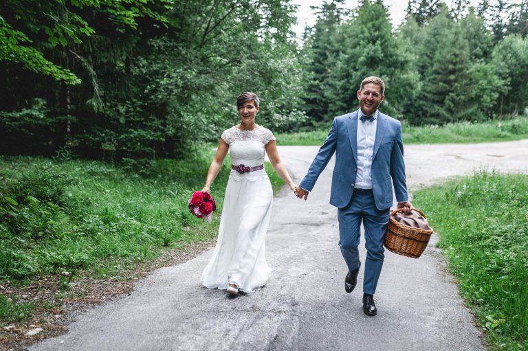 Das Brautpaar mit Brautstrauß und Picknickkorb auf dem Weg in den Wald des Almbad Huberspitz