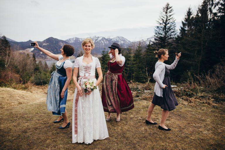 Braut lacht in die Kamera, im Hintergrund tanzen drei Frauen im Dirndl - Hochzeitstanz vor Bergpanorama im Almbad Huberspitz