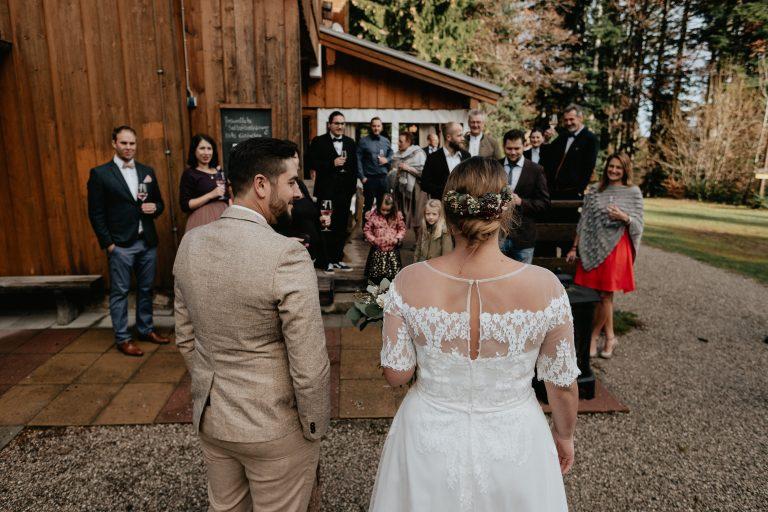 Brautpaar spricht zu seinen Gästen, die ihnen draußen mit Glas in der Hand lächelnd vorm Almbad Huberspitz gegenüberstehen