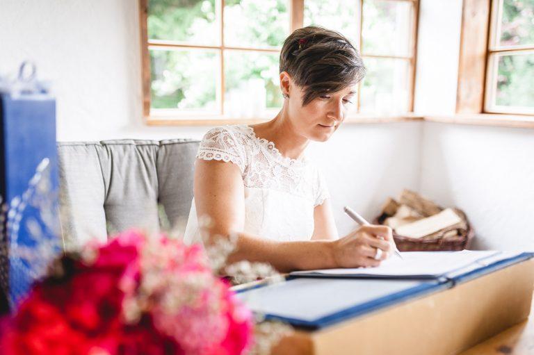 Die Braut unterzeichnet die Urkunde am Trautisch des Almbad Huberspitz