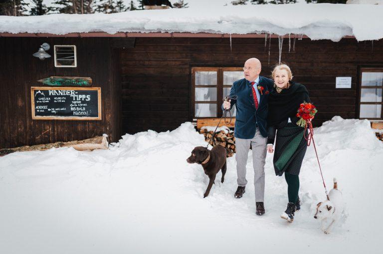 Brautpaar im besten Alter mit je einem Hund an der Seite, im Schnee vor dem Almbad Huberspitz