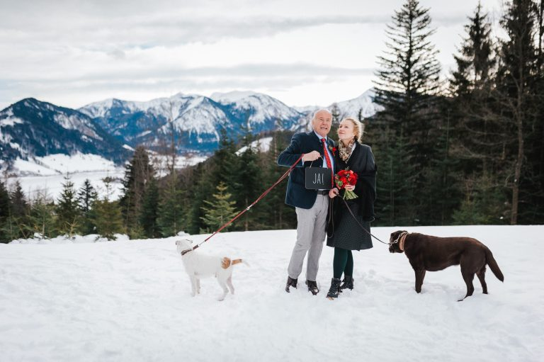 Brautpaar mit Hunden und JA-Schild im Almbad Huberspitz mit Blick auf den Schliersee und das dahinter liegende Alpenpanorama