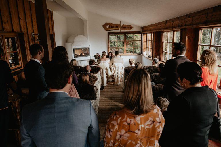 Blick in den Alm-Trausaal des Almbad Huberspitz: Am Trautisch vorne sitzt das Brautpaar bei der Trauung, hinten sitzen Freunde und Familie