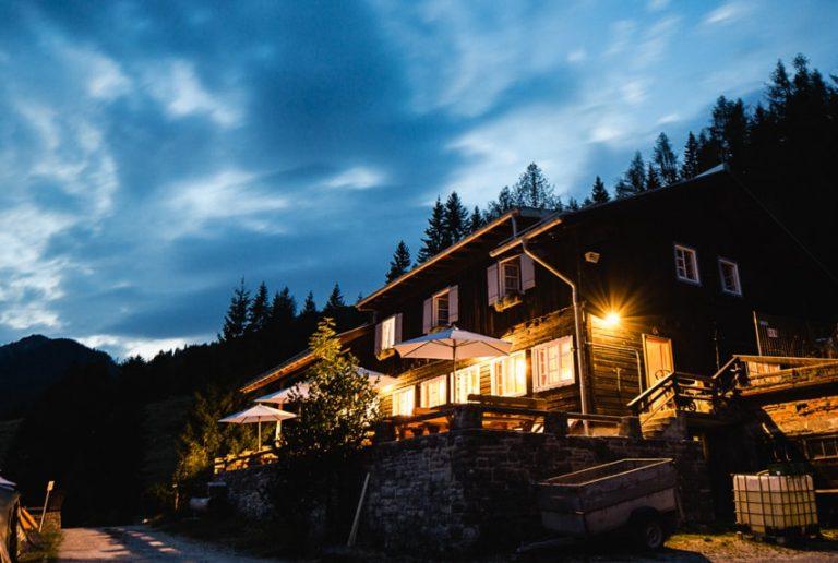 beleuchtetes Almbad Sillberghaus bei Abenddämmerung