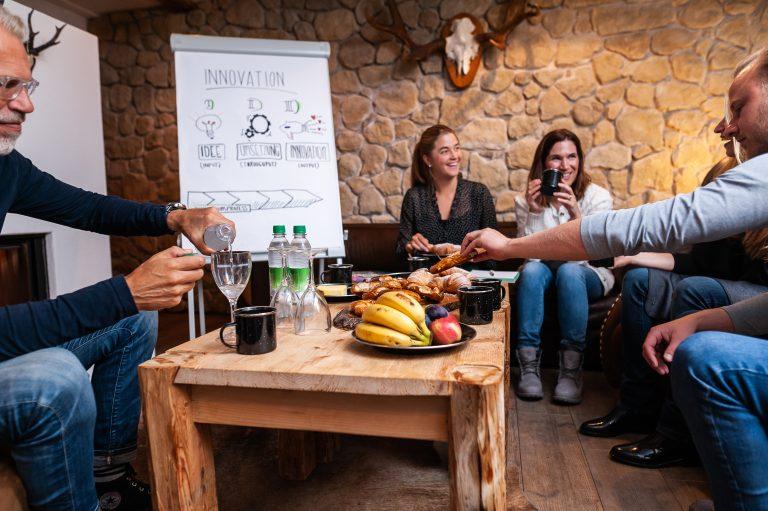 Workshop-Teilnehmer sitzen um den Tisch, mit frischem Obst und Früchten, vor dem Flipchart im Dorfbad Tannermühl