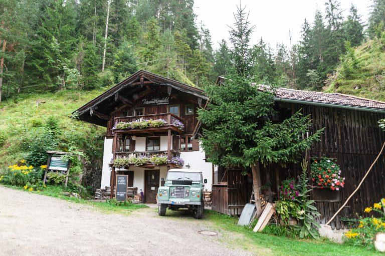 Frontansicht des Dorfbad Tannermühl, mit altem Geländewagen vor der Tür