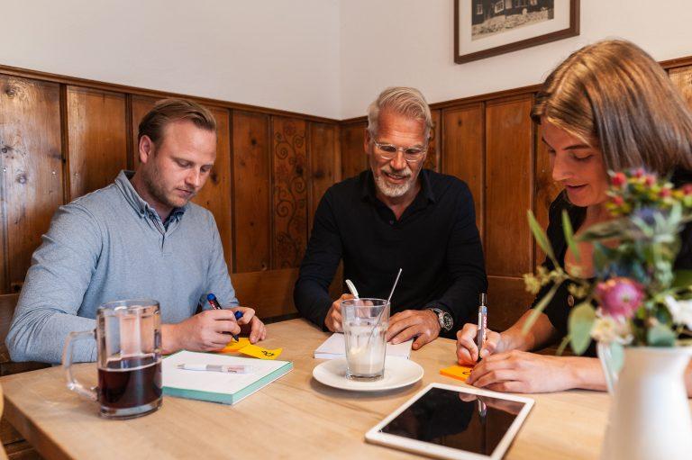 Drei Tagungsteilnehmer am Brainstorming als Gruppenarbeit in einer der beiden Gast-Stuben des Almbad Sillberghaus