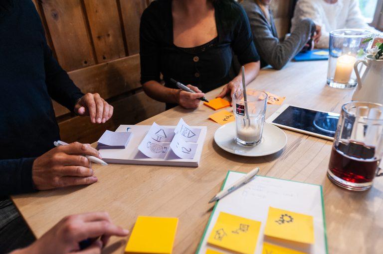Seminarteilnehmer vor Post-Its und Notizzettel zur Gruppenarbeit in einer der beiden Gast-Stuben zur exklusiven Nutzung