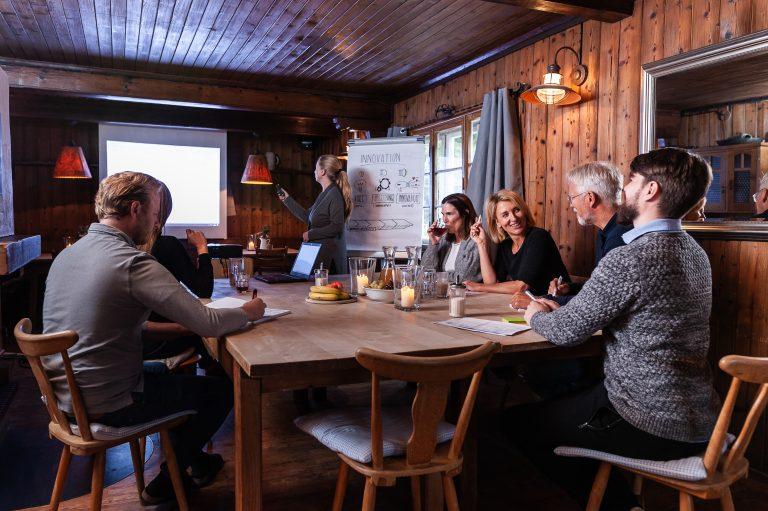 Tagungsgruppe im Kaminzimmer des Almbad Sillberghaus, mit Leinwand und Flipcharts