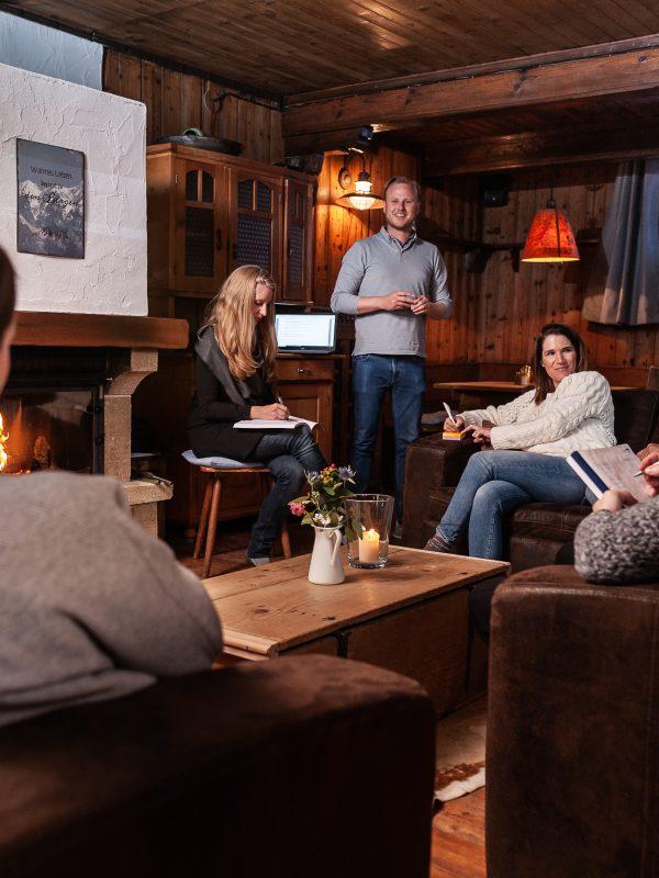 Workshop-Teilnehmer in Ledersessel, versammelt um Flipchart im Kaminzimmer des Almbad Sillberghaus