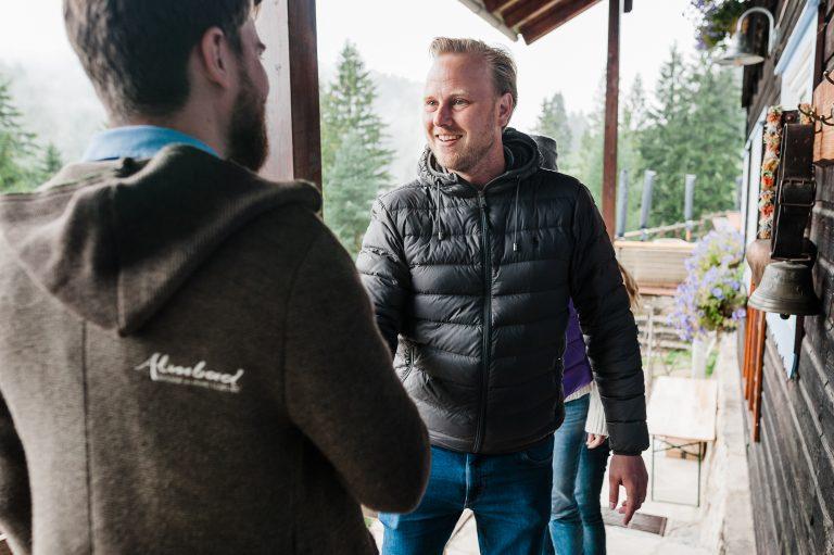 Mitarbeiter des Almbad Sillberghaus begrüßt die Tagungsgruppe nach ihrem Aufstieg zur Hütte Almbad Sillberghaus
