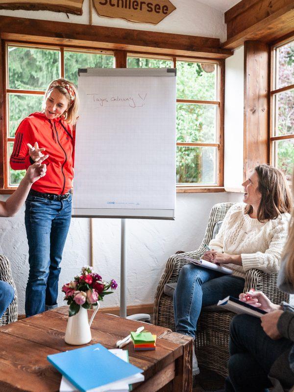 Brainstorming im Wintergarten des Almbad Huberspitz - Trainerin schreibt am Flipchart mit
