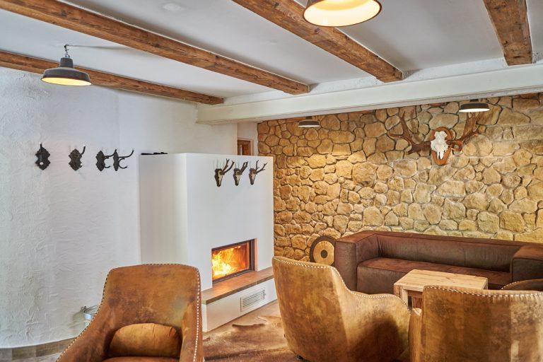 Kaminstube im Dorfbad Tannermühl mit loderndem Kaminfeuer und gemütlichen Ledersesseln