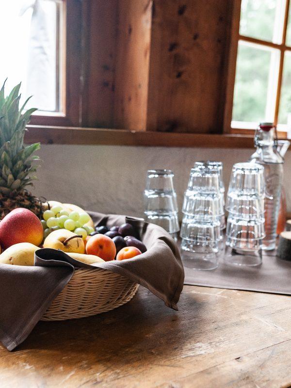 Obst und Getränkebar im Almbad Huberspitz, im Vordergrund ein üppiger Obstkorb mit Ananas, Äpfel, Birnen, Trauben